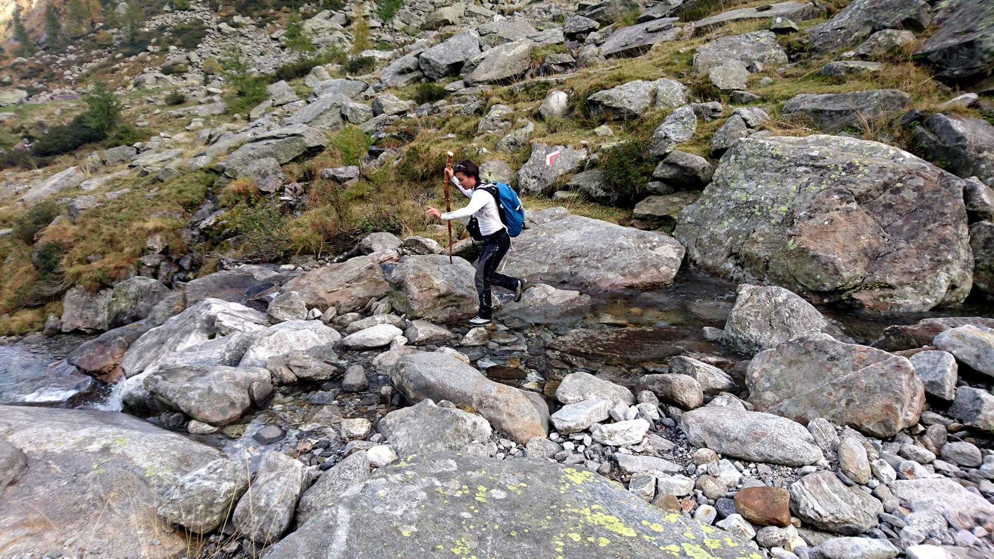 Erica guada il torrente con agilità dotata del suo bastone nuovo fiammante