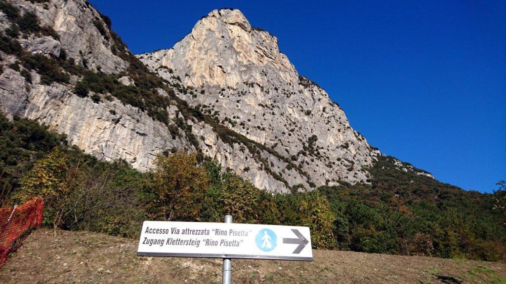 La bella parete del Picol Dain e il cartello che dal parcheggio ci guida verso l'attacco della nostra ferrata