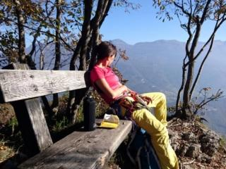 Erica si gode il riposo e il paesaggio dalla panchina di vetta.