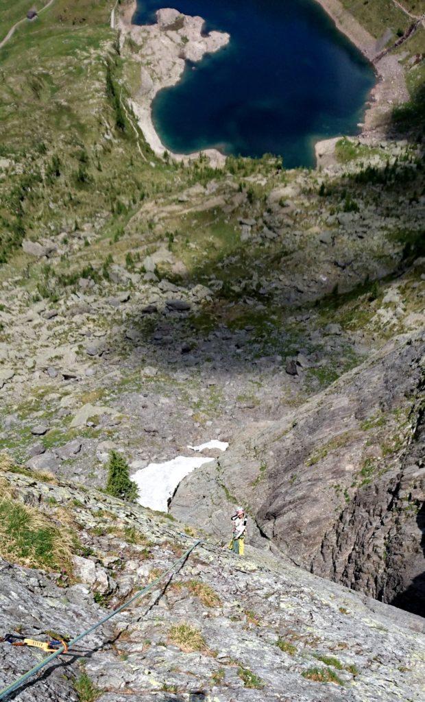 sulla placca di IV grado, con il lago di Pescegallo la cui vista ci terrà compagni per tutta la scalata