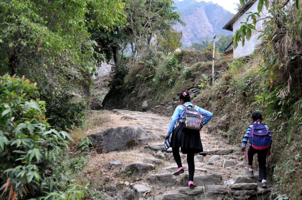 due bambine in uniforme affrontano il sentiero verso la scuola che si trova in cima alla collina. Tutti i giorni si fanno un'ora di cammino in salita e in discesa!