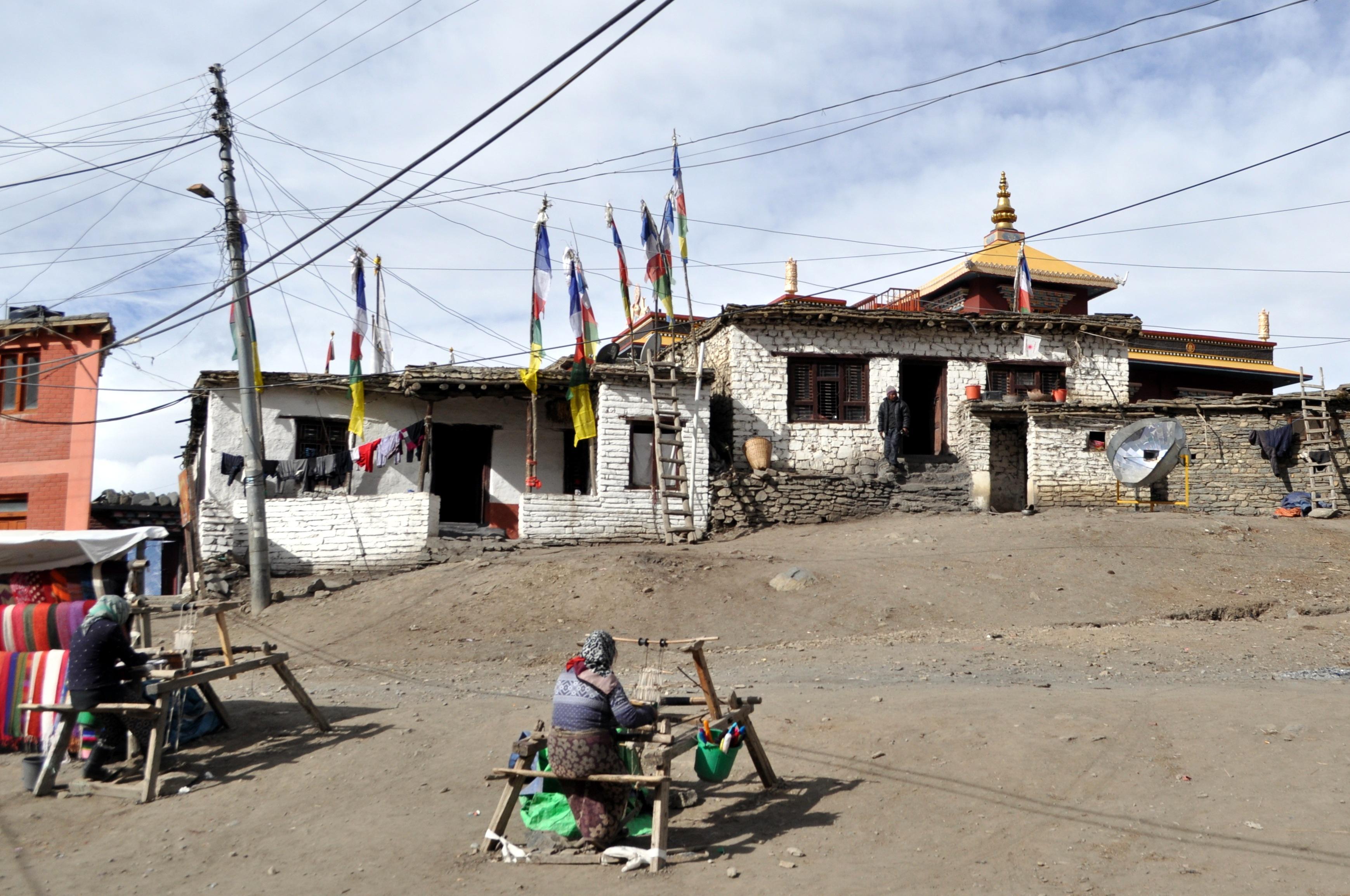 donne filano sciarpe e stole in lana, sulla strada principale di Muktinath