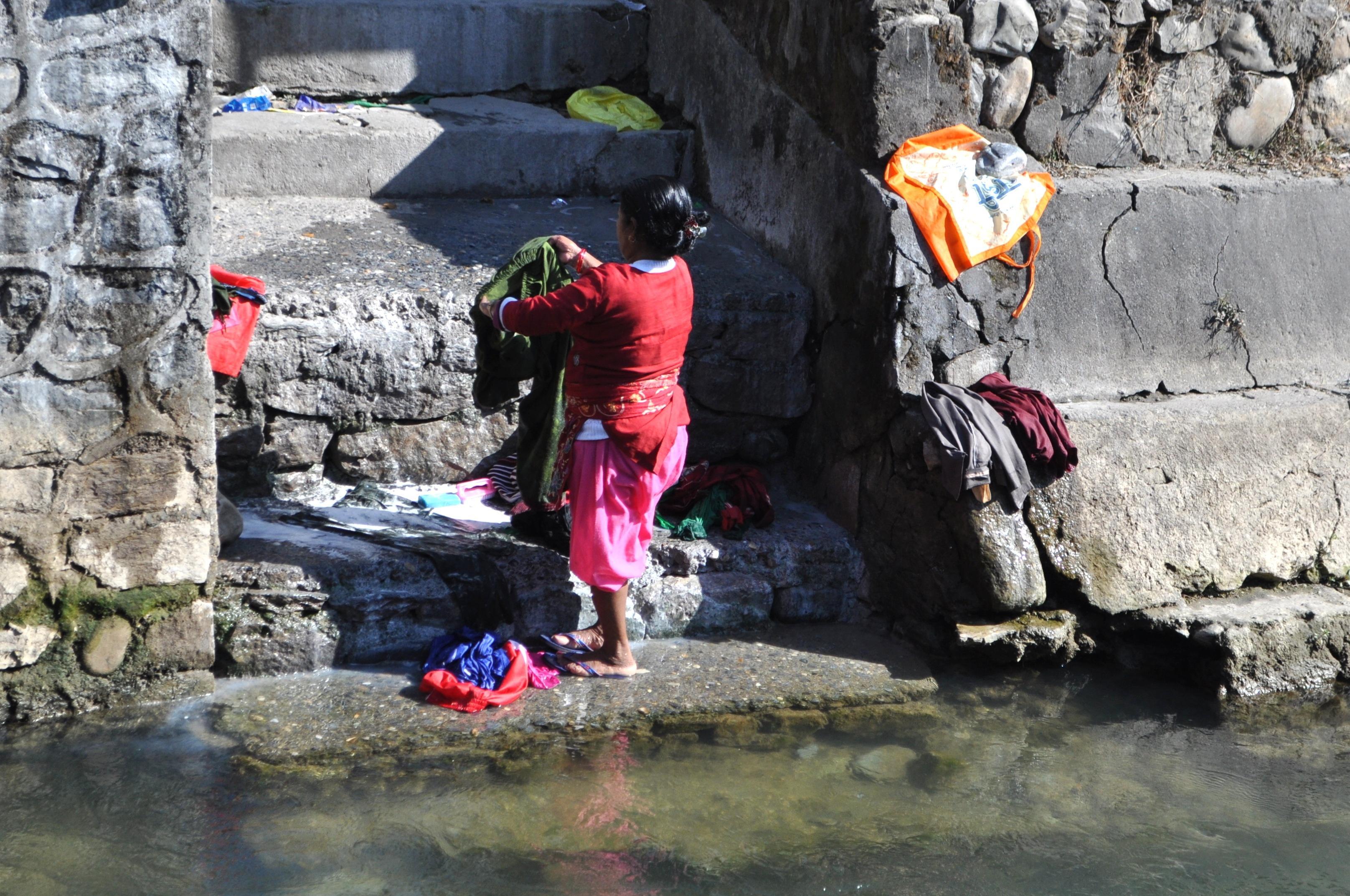 una donna lava i panni in un corso d'acqua (ovvero: i colori non conoscono miseria)