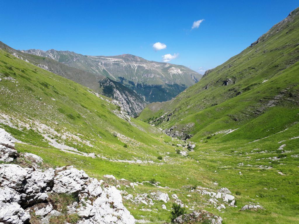 la valle nella sua parte più alta, sullo sfondo il Monte Sibilla tagliato dai tornanti della strada