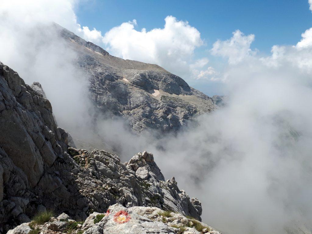 i segnavia della Ferrata Danesi, e le nubi che cominciano ad addensarsi sulla cima
