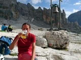 Erica si gode la sua birrozza davanti alla campana del rifugio Alimonta