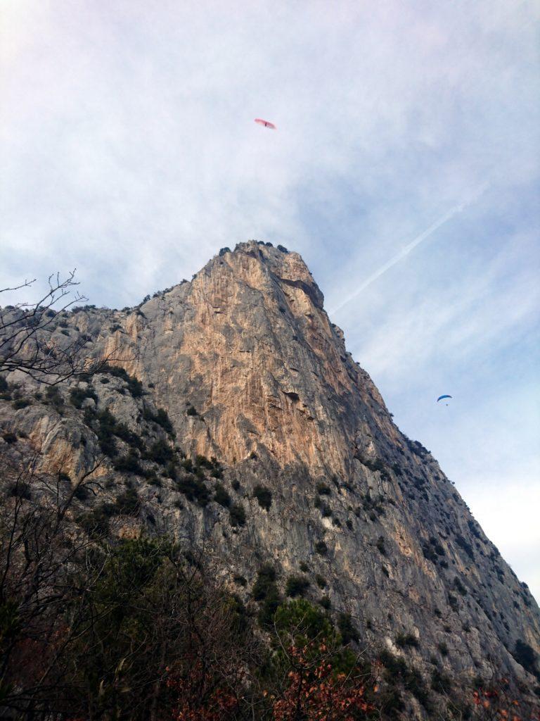La fantastica parete verticale del Piccolo Dain visto dal sentiero di discesa, con tanto di parapendii svolazzanti