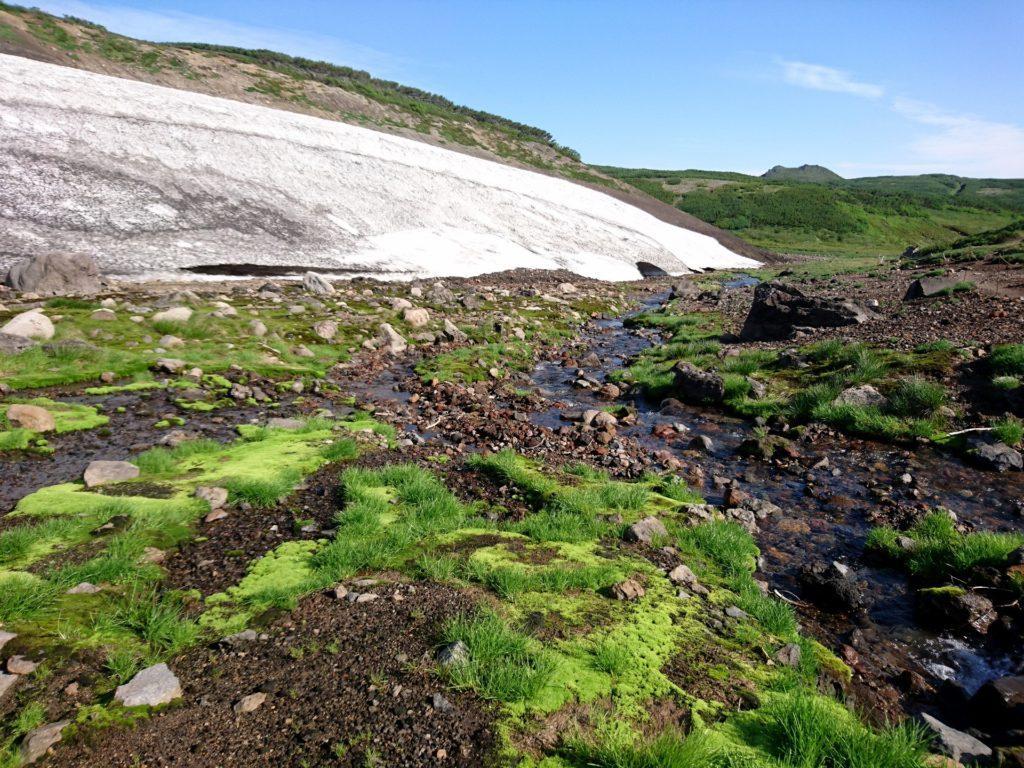 prima di riguadagnare la valle, qui solcata da corsi d'acqua e con qualche nevaietto
