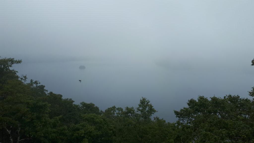 il lago di Mashu coperto dal vapore e dalle nubi: si intravede l'isoletta al suo centro