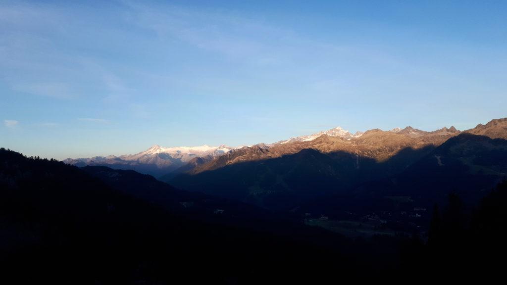Sul lato opposto della valle, il sole comincia ad illuminare il gruppo della Presanella e dell'Adamello