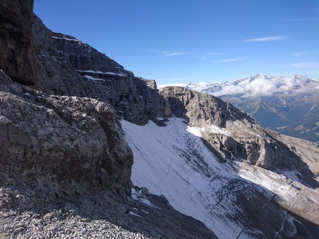 si aggira il pilastrone scendendo sulla destra e stando vicino alle rocce. Attenzione al terreno