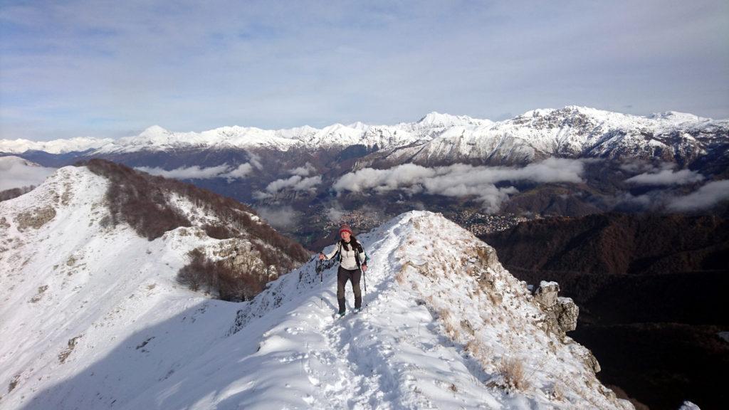Erica giunta in cresta e sullo sfondo da destra lo zucco Campelli, al centro il Tre Signori e a sinistra il Legnone