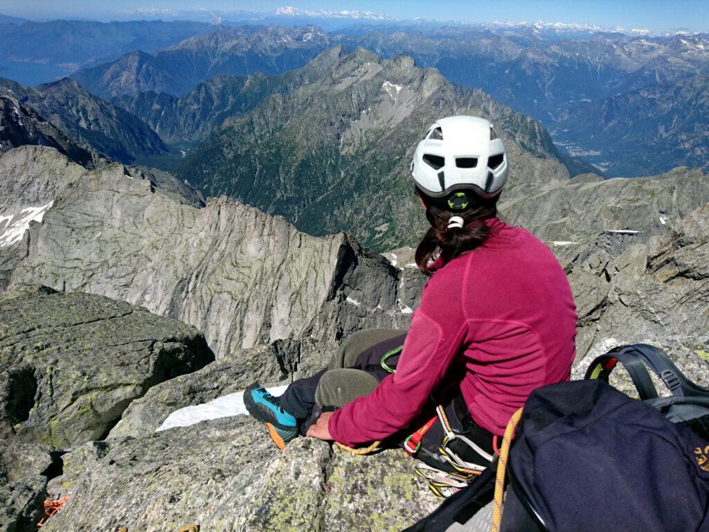 Erica si gode il magnifico panorama dalla vetta del Badile in una giornata di cielo totalmente terso