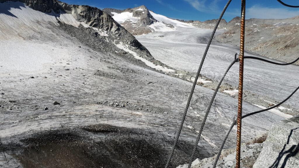 l'incredibile ritirata del ghiacciaio sotto al Rifugio Lobbia Alta, che lascia scoperta una porzione di terra e detriti