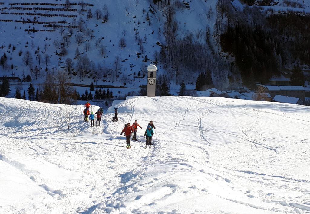 il campanile della chiesa di Isola svetta sulla neve, mentre il folto gruppetto si approssima a partire