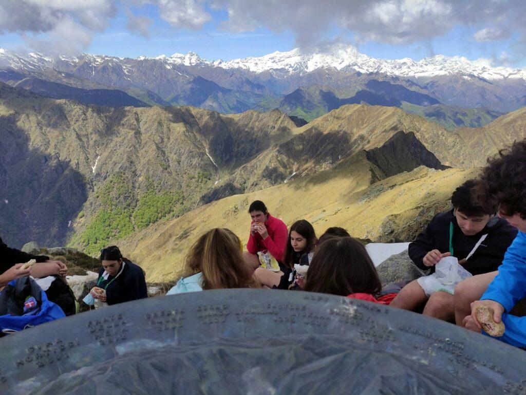 La rosa delle cime, un gruppo scout che pranza in vetta e il Monte Rosa sullo sfondo