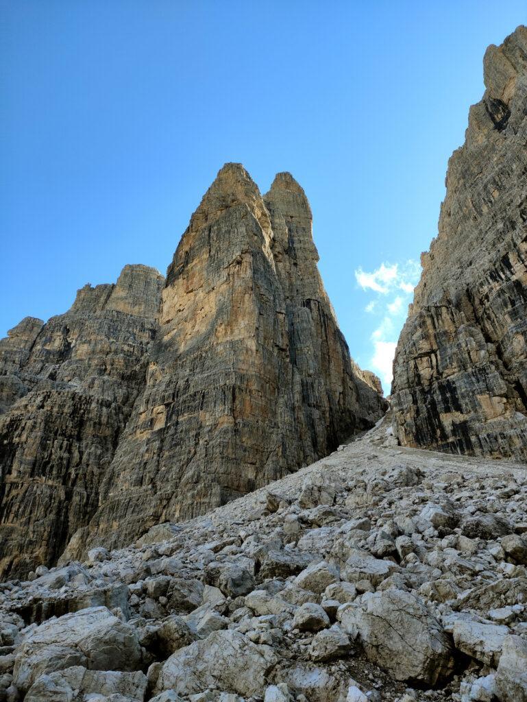 risalendo il ghiaione verso Bocca di Brenta si passa di fianco al Campanile Basso: una cordata è impegnata nei primi tiri di quella che potrebbe essere la Fermann