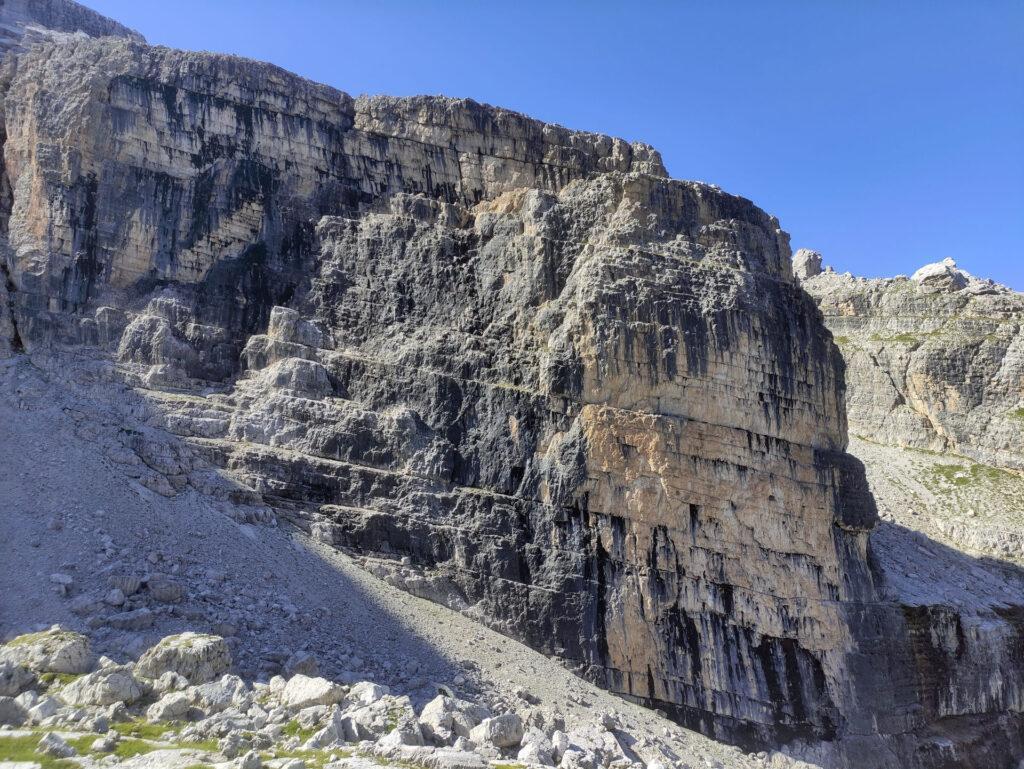 La via si svolge sulla parte più bassa della bastionata, lungo la parte di roccia nera