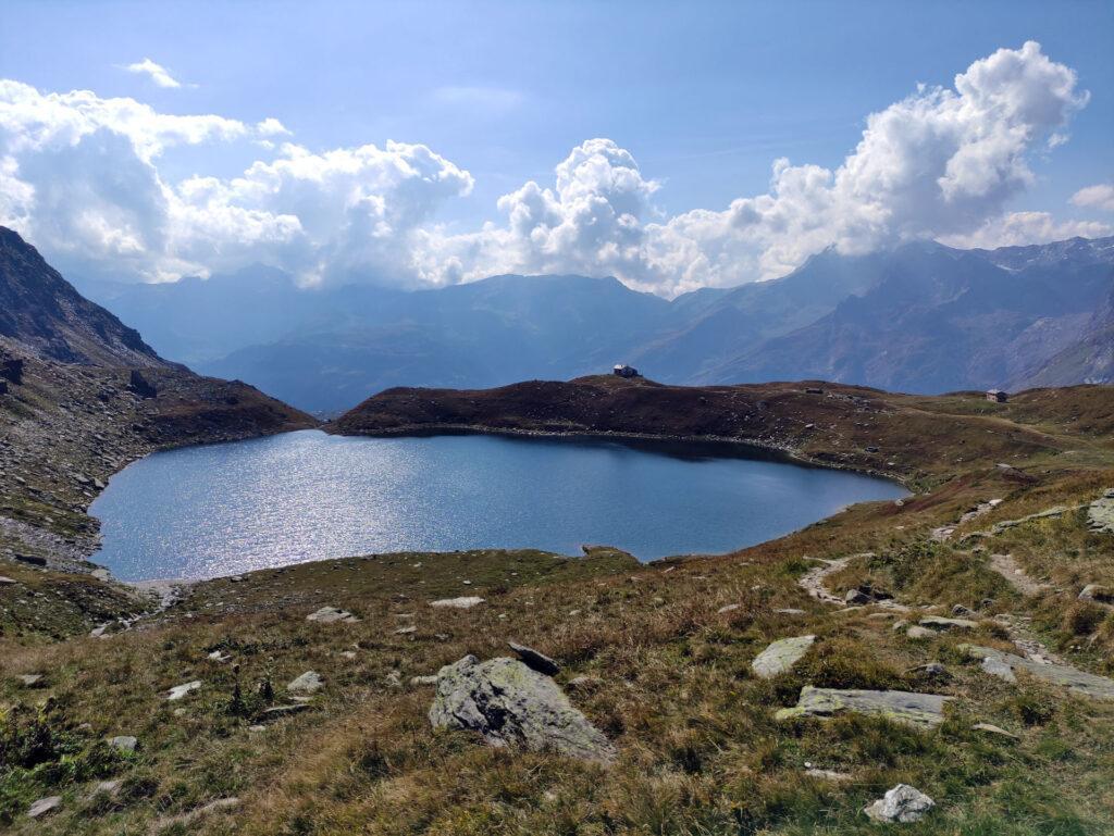 Dopo lunghe, ripide e faticose pietraie eccoci finalmente al lago di Emet dietro a cui sorge il rifugio Bertacchi
